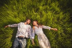 Couple in love lying on grass royalty free stock photos