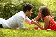 Couple in love lying on the grass in the park Royalty Free Stock Images