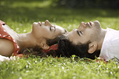 Couple in love lying on the grass in the park Stock Photos