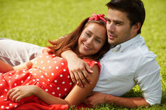 Couple in love lying on the grass in the park Stock Images