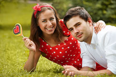 Couple in love lying on the grass in the park Stock Photo