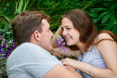 Couple in love lying in the grass on a summer meadow Royalty Free Stock Photos