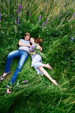 Couple in love lying in the grass on a summer meadow Stock Photo