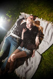 Couple in love lying on plaid on lawn at night Royalty Free Stock Images