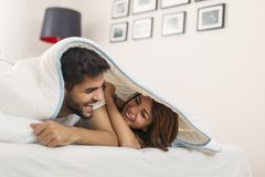 Couple in love lying under the sheets stock images