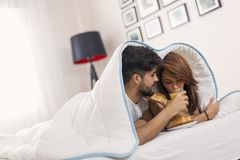 Couple in love lying under the sheets, having fresh croissants and orange juice for breakfast in bed and enjoying the weekend stock photography
