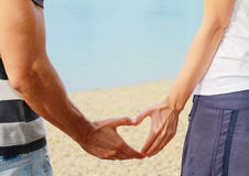 Couple in love Making Heart Shape With hands on the beach. Royalty Free Stock Images