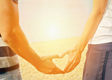 Couple in love Making Heart Shape With hands on the beach. Stock Photos