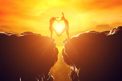 Couple in love making heart shape over precipice. Happy couple making heart shape over precipice between two rocky mountains at sunset. Love unique concept Stock Images