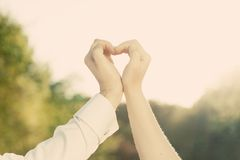 Couple in love making a heart shape with their hands outdoors. Stock Photos