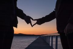 Couple in love making heart silhouette Royalty Free Stock Photos