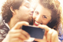 Couple in love making a selfie while him giving her a kiss. In the city Royalty Free Stock Image