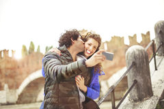 Couple in love making a selfie while him giving her a kiss Stock Image