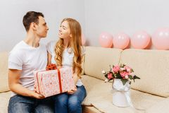Couple in love, man gives a gift, woman sits at home on the sofa, concept of women`s day stock photography