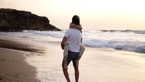 Couple in love. Man in shirts turning around his lovely woman on beach and sensually kissing. Full length view of happy