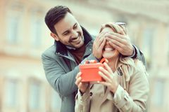 Couple in love. Man surprising his girlfriend with a gift Stock Images