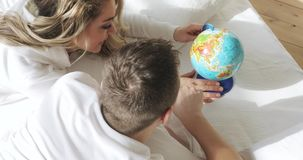 Couple in love in bed are looking at globe spinning it and pointing at random choosing a place to travel on honeymoon stock footage