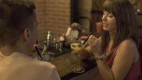 Couple in love man and woman drinking alcoholic cocktail sitting at bar counter while romantic date in restaurant. Young. Couple drinking cocktail while party stock video footage