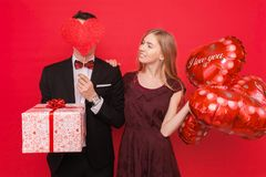 Couple in love, man and woman give each other gifts, holding gift boxes and balloons, on a red background Valentine`s Day concept stock images