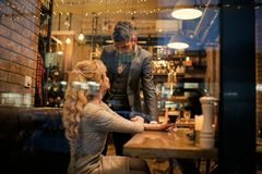 Couple in love meet at restaurant. Valentines day with woman and bearded man. Meet, proposal and anniversary. Couple in love meet at restaurant. Valentines day stock image