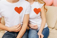 Couple in love, man and woman in white T-shirts, holding paper hearts, at heart level, sitting on the sofa at home royalty free stock photos