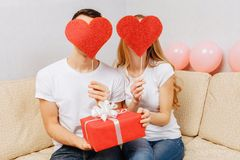 Couple in love, man and woman in white t-shirts, holding paper hearts, sitting at home on the couch. Valentine`s day concept stock image