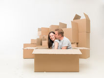 Couple in love moving home. Couple sitting in a box, kissing and having fun after moving in new home royalty free stock images