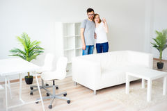Couple in love in a new apartment. Young smiling couple showing keys to new home Stock Photography