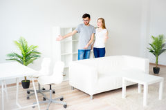 Couple in love in a new apartment. Young smiling couple showing keys to new home Stock Images