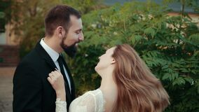 Couple in love newlyweds. Bride in wedding dress puts her hands on groom's chest stock footage