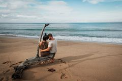 Couple in love on the ocean. Couple hugging by the sea. Loving couple. Guy and girl kissing. Boy and girl on the beach. A lonely couple. Man and woman on the royalty free stock photos