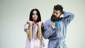 Couple in love in pajama, bathrobe stand back to back. Couple, family on sleepy faces in morning routine. Girl with. Dumbbell, man with coffee cup, isolated on stock video