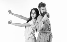 Couple in love in pajama, bathrobe stand isolated on white background. Couple, family on sleepy faces, full of energy. Girl with dumbbell, men with coffee cup royalty free stock photography