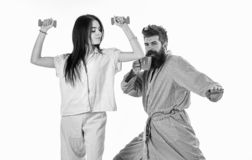 Couple in love in pajama, bathrobe stand isolated on white background. Girl with dumbbell, man with coffee cup. Couple in love in pajama, bathrobe stand isolated royalty free stock images