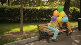 A couple in love in the park with colorful balloons stock video