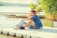 Couple in love on the pier, sitting Royalty Free Stock Images