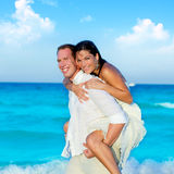 Couple in love piggyback playing in beach. Couple in love piggyback playing in a beach at blue Mediterranean Royalty Free Stock Photos