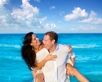 Couple in love piggyback playing in beach. Couple in love piggyback playing in a beach at blue Mediterranean Stock Photo