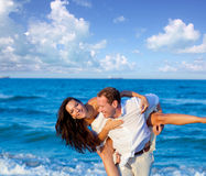 Couple in love piggyback playing in beach. Couple in love piggyback playing in a beach at blue Mediterranean Stock Photography