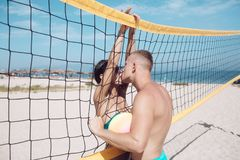 Couple in love play volleyball on sunny beach. Summer vacation and travel on holiday in Miami. Love and flirting of stock photos