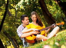 Couple in love playing acoustic guitar Royalty Free Stock Image