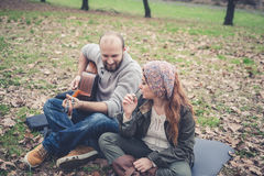 Couple in love playing serenade with guitar Royalty Free Stock Images