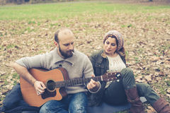 Couple in love playing serenade with guitar Stock Photography