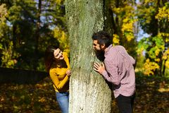 Couple in love plays behind tree in autumn park. Man and women with excited faces on nature background. Girl and bearded guy or lovers on a date look at each stock image