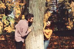 Couple in love plays behind tree in autumn park. Man and women with excited faces on nature background. Girl and bearded guy or lovers on a date look at each royalty free stock photo
