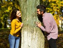 Couple in love plays behind tree in autumn park. Man and women with happy faces on autumn trees background. Young family and autumn concept. Girl and bearded royalty free stock photos