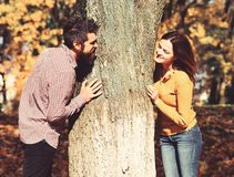 Couple in love plays behind tree in autumn park. Man and women with happy faces on autumn trees background. Young family and autumn concept. Girl and bearded stock photography