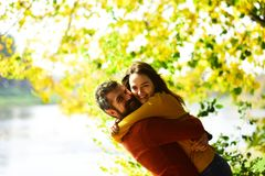 Couple in love plays and cuddles in park by river. Girl and bearded guy or happy lovers on a date hug. Relationship and fall time concept. Man and women with stock image