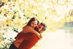 Couple in love plays and cuddles in park by river. Girl and bearded guy or happy lovers on a date hug. Relationship and fall time concept. Man and women with stock photos