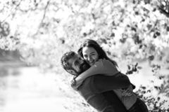 Couple in love plays and cuddles in park by river. Girl and bearded guy or happy lovers on a date hug. Relationship and fall time concept. Man and women with royalty free stock image